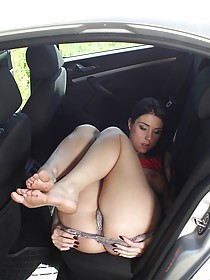 Red and black get-up brunette fingering her juicy pussy in a car