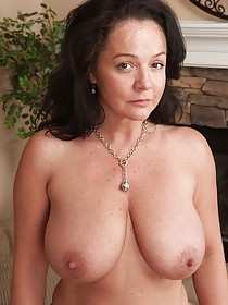 Busty MILF brunette shows off her wrinkly pussy on her couch