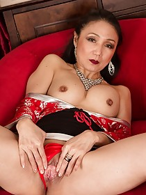 Luxurious Asian MILF showing off her alluring pussy on a red chair