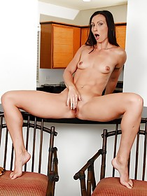 Long-legged brunette with tats fingering her pussy on a table