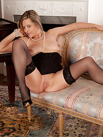 Blond-haired MILF in black stockings teasing her pussy by the piano