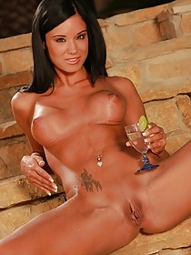Orange get-up tanned brunette masturbating after finishing her cocktail