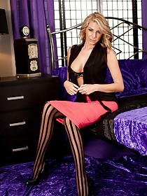 Striped stockings blond-haired MILF shows her smooth pussy on a bed
