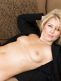 Businesswoman GILF teasing her completely smooth pussy on a couch