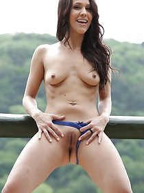 Wavy-haired brunette teasing her tight little pussy next to a scenic view